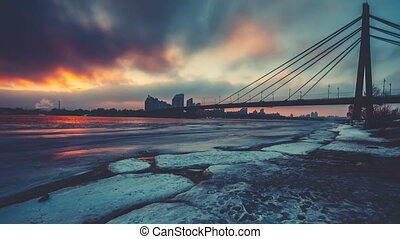 coloured evening clouds float over half frozen Dnipro river...