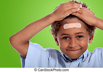 coloured little boy with plaster on his forehead against...