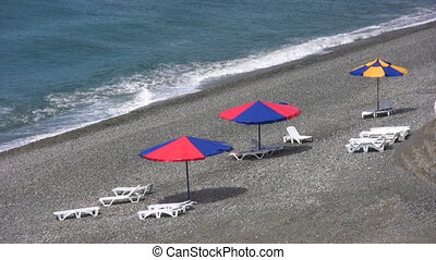 umbrellas and beds on pebble beach with sea surf