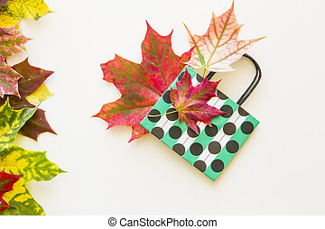 Colourful autumn leaves and polka dot paper bag on white background. Flat lay. Top view