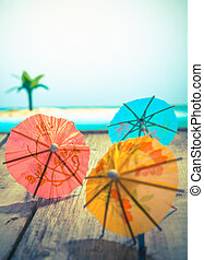 Colourful cocktail or paper umbrellas lying on a wooden deck with a tropical seaside backdrop, conceptual for partying and festivity