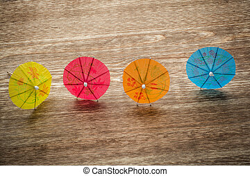 Colourful cocktail umbrellas lying on a wooden backdround, conceptual for partying and festivity