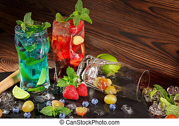 Colourful cocktails with mint, lime, ice, berries on the wooden background. Refreshing summer beverages. Copy space.
