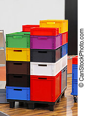 Colourful plastic crates and boxes at pallet