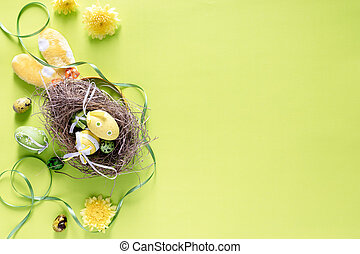 Colourful Easter eggs in birds nest with festive decoration on bright lime green background, top view- image