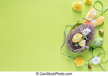 Colourful Easter eggs in birds nest with festive decoration on green background, top view- image