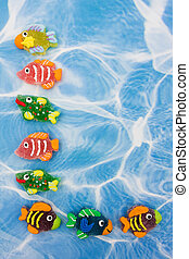 A large group of colourful fish sitting on blue water background, colourful fish border