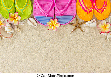 Colourful Flip Flops in the sand with shells and frangipani flowers. Summertime on beach concept.