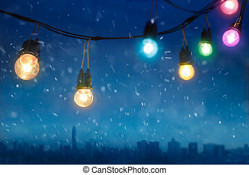 Colourful glowing christmas lights in snowfall on the dark...