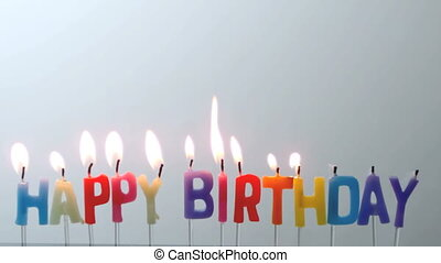 Colourful happy birthday candles being blown out in slow motion