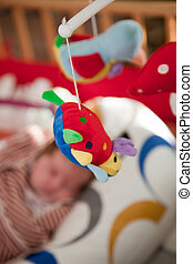 Colourful soft mobile toy on a baby crib