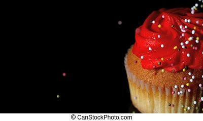 Colourful sprinkles pouring onto cupcake on black surface in...