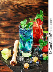 Colourful sweet cocktails with mint, lime, ice, berries on the wooden background. Refreshing summer beverages. Copy space.