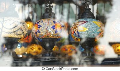 Colourful turkish lamps from glass mosaic glowing. Arabic multi colored authentic retro style lights. Many illuminated moroccan craft lanterns. Oriental islamic middle eastern decor. Shiny folk shop.