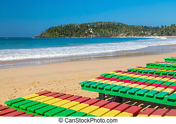 Colourful wooden deck chairs on Unawatuna beach in Sri Lanka.