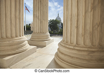 Columns of the Supreme Court with an American flag and the US Capitol in the background