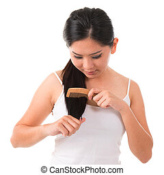 Young Asian female combing her hair over white background