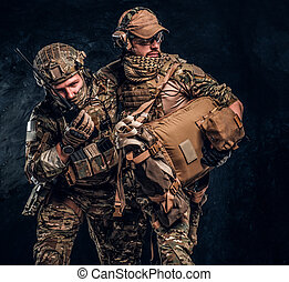 Combat conflict, special mission, retreat. Military medic rescues his wounded teammate carrying him off the battlefield.