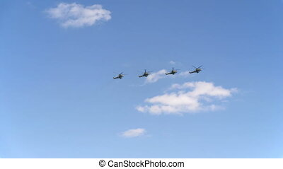 Combat helicopters Mi-24 fly in blue sky