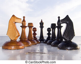 Combination from chessmen on a table with a kind on the sea