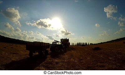 Combine And Tractor Driving Away At Field - This is a rear...