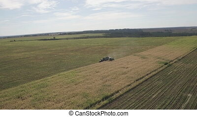 Combine harvester unloading corn in tractor tow while...