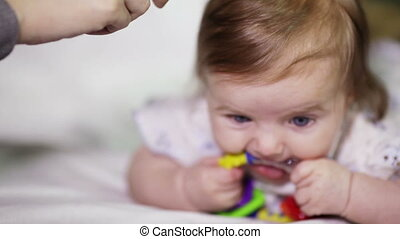 Combing baby chewing on rattle
