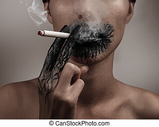 Combustion from smoking - A woman smokes a cigarette, her...