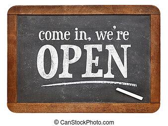 Come in, we are open - invitation on a vintage slate blackboard