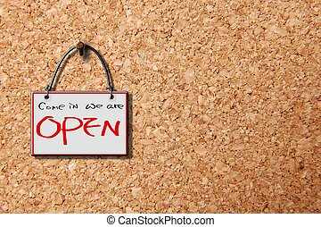 come in we are open hanging sign isolated on wall