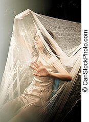 come out to light - young woman in garden with veil cover...