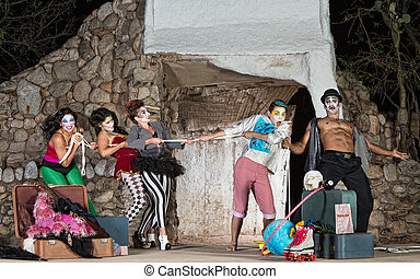 Group of silly cirque clowns playing tug-of-war