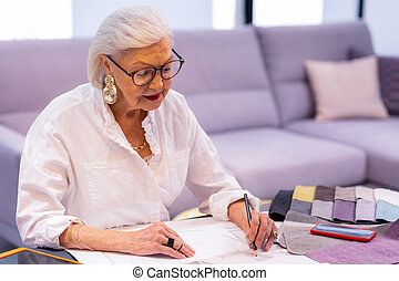 Comely smiling elderly woman in glasses making designer sketch