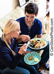 comendo alimento, par, jovem, tradicional, asiático, lar, caucasiano