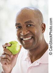 comendo maçã, meio, câmera, verde, sorrindo, envelhecido, homem