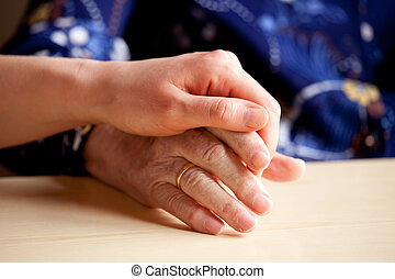 Comfort - A young hand comforts and elderly hand