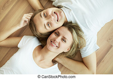 Above angle of young couple lying on the floor and looking at camera
