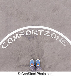 Comfort zone text on asphalt ground, feet and shoes on floor, personal perspective footsie concept