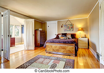 Bedroom with hardwood floor rug. Furnished with antique dresser cabinet and carved wood bed. Room has a walkout bright office room