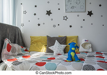 Comfortable small bed with toys in children's bedroom