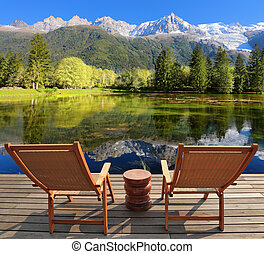 Comfortable lounge chairs on wooden platform for rest and...