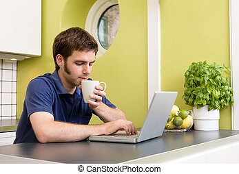 Comfortable Online - A young man uses the computer in the...
