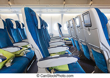 Comfortable seats in cabin of huge aircraft with screens in...
