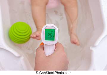 Comfortable water temperature in the bathroom. female hand with infrared thermometer checks the water temperature