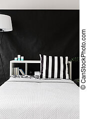 Large comfortable white bed standing on the background of the black sheet