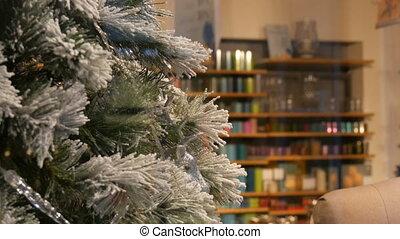 Comfortably decorated Christmas shop window, beautiful Christmas tree close-up
