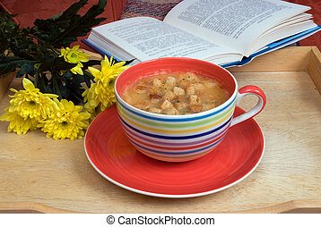 Comforting - A large cup with soup on a tray