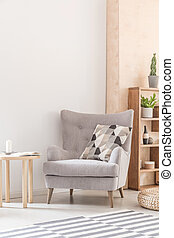 Comfy armchair with patterned pillow next to a wooden coffee table in a living room interior. Real photo. Place your poster