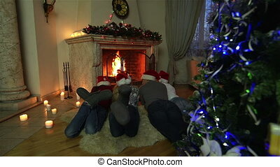 Comfy Christmas - Family of four lying in front of the...