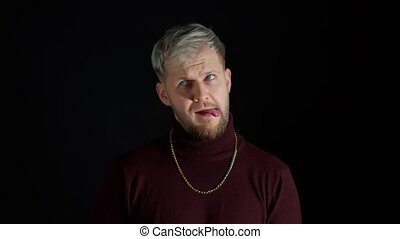 Comical stupid stylish man with blue eyes in trendy clothes making funny awkward silly face grimace, playing fool, showing tongue, pretending to be dumb, brainless on black background. Modern fashion